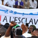"""People hold a banner reading """"No to slavery"""" during a demonstration against discrimination in Nouakchott on April 29, 2015. Thousands of descendants of Moorish slaves in Mauritania, known as the """"Haratin"""", protested in Nouakchott on the evening of April 29 against discrimination and to demand justice and equality for the Haratin. AFP PHOTO / STRINGER"""