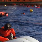 14.11.16 View from a rescue boat of the SAR-Team. A woman in a rubber boat waiting to be rescued by the SAR-Team. Other migrants holding on to floating devices in the water.